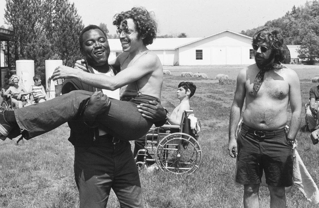 Fotografía en blanco y negro de tras hombres, uno hombre caucásico con cabello rizado y gafas está en los brazos de otro hombre afrodescendiente, quien lo lleva cargando, mientras otro hombre, caucásico con pañoleta al rededor del cuello, los mira.