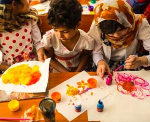 Tres niñas pintando con temperas en hojas de papel, las tres son alumnas de la escuela afgana Fatima Khalil con cuadernos en sus manos