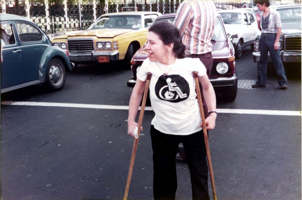 Fotografía de una mujer de edad media, cabello oscuro, que se encuentra de pie, mirando hacia la derecha, apoyada en dos muletas, que lleva puesta una playera con un signo de discapacidad que al centro tiene un puño cerrado.