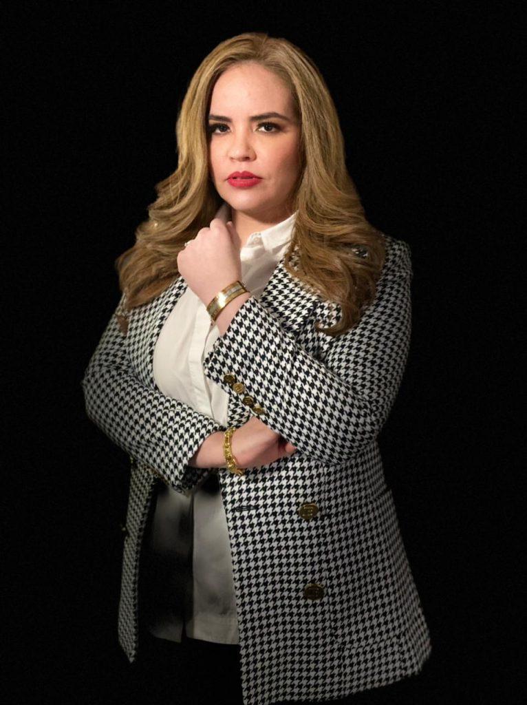 Fotografía de estudio de Esmeralda Bastidas, una mujer joven con cabello largo y ondulado de color rubio, lleva puesto un abrigo a cuadros blanco con negro y una blusa color blanca debajo, se encuentra seria viendo de frente a la cámara.