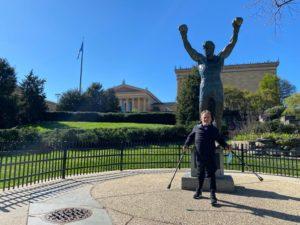 Jean Maggi se encuentra de pie con los brazos abiertos frente a una estatua, se encuentra vestido con chamarra rompe vientos y pantalón de color negro.