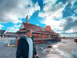 Jean Maggi se encuentra de pie frente a un restaurante, se encuentra vestido con una chamarra azul marino y una camisa azul claro.
