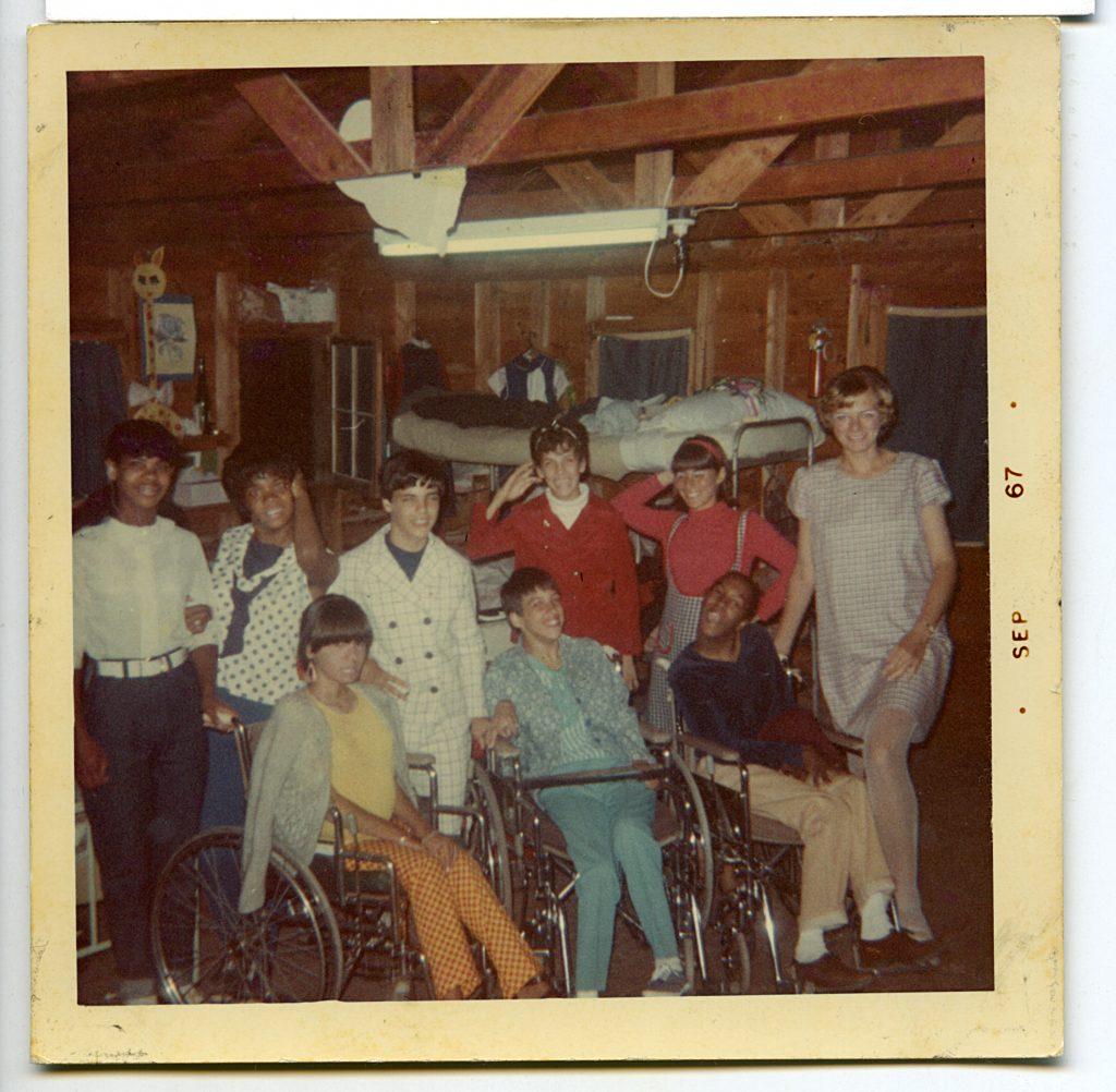 Fotografía en donde aparecen nueve personas, cuatro de ellas con discapacidad motriz, dos personas afrodescendientes, y tres personas caucásicas, todas sonriendo frente a la cámara.
