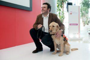 Fotografía de Juan Serrat, un hombre de mediana edad que utiliza un saco café, camisa blanca y pantalón negro, se encuentra hincado a lado de Leire, un perro perro de asistencia de raza labrador de color beige