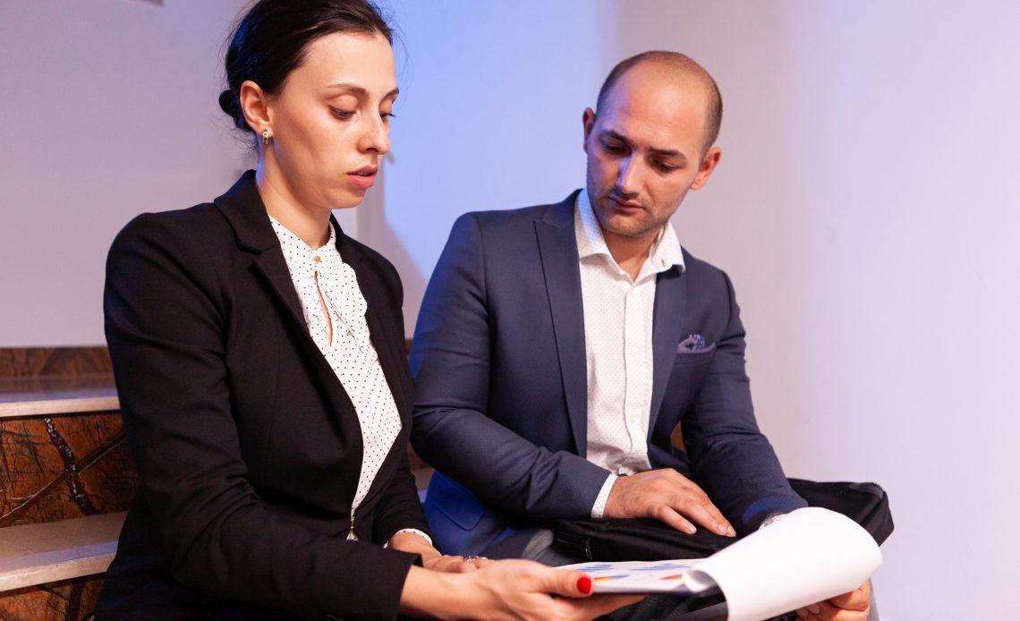 Fotografía de dos personas conversando, una mujer que sostiene un test en su mano, vestida de saco negro y blusa blanca y un hombre con saco azul y camisa blanca que espera ver sus respuestas.