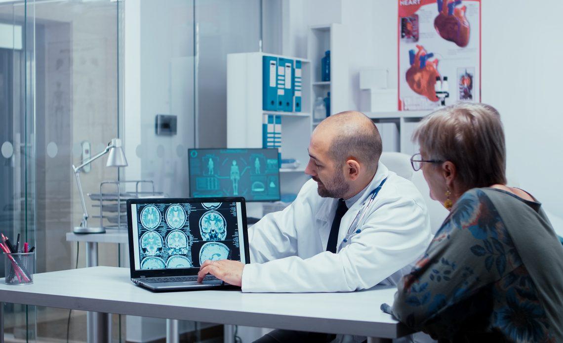 Fotografía en la que aparece un doctor mostrando una tomografía a una señora de edad adulta dentro de un consultorio color blanco.