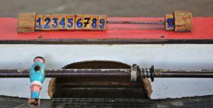 Fotografía del portero de un futbolito de madera, juego inventado por un poeta español, donde se aprecia un contador de goles. El portero, pintado de color azul agua, está sostenido en una de las barras de metal características de este popular juego.