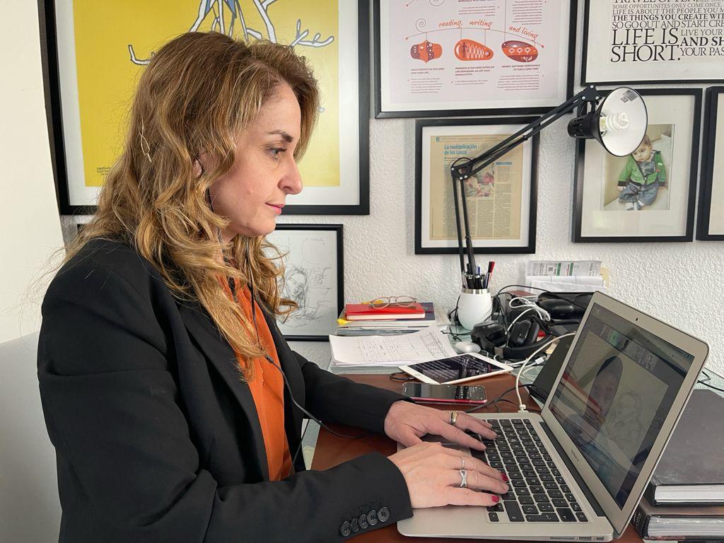 Fotografía de Bárbara Anderson, una mujer de mediana edad, cabello rubio, que se encuentra sentada frente a su computadora, detrás de ella aparecen varios cuadros decorativos, lleva puesto un saco color negro, una blusa color naranja y se encuentra con semblante serio.