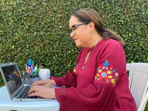 Fotografía de D'Artigues frente a su computadora, al fondo tiene una pared con plantas, lleva puesta una blusa de color roja con flores bordadas en la manga holgada, Katia es una mujer de mediana edad que utiliza anteojos color negro y tiene expresión sonriente.