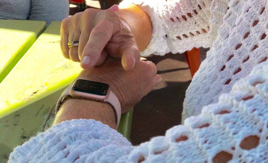 Fotografía de las manos de una señora sobre una mesa de madera color verde, la señora lleva puesta una blusa blanca y tiene su dedo sobre un apple watch, un reloj inteligente con correa rosa.