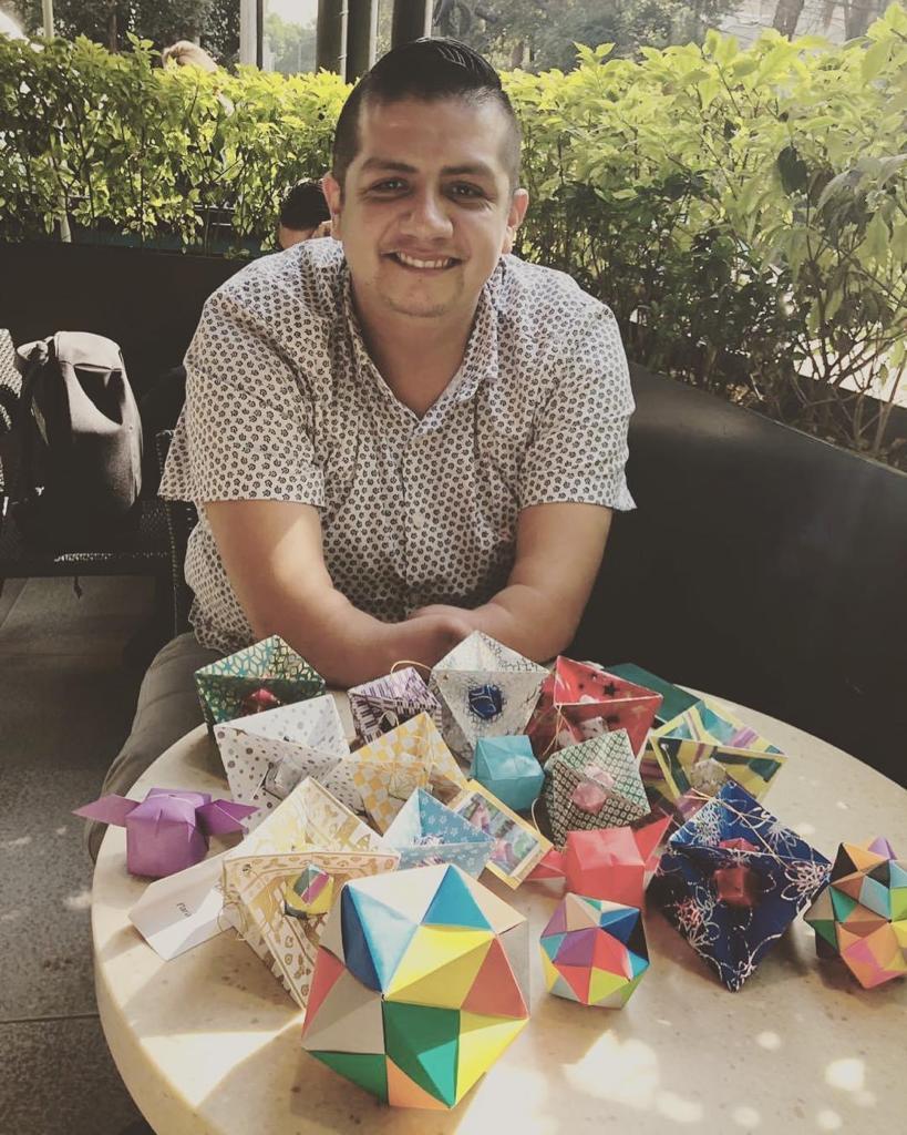 Fotografía de Tony Valdés sentado ante una mesa en donde se aprecian varias de las figuras de origami que suele crear, algunas de gran colorido. El joven de 32 años luce sonriente. A su espalda está una jardinera con arbustos.