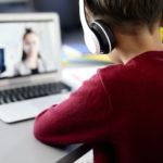 Fotografía de un niño sentado en un escritorio de espalda a la cámara que se encuentra mirando hacia el monitor de una computadora, trae puesto un suéter de color rojo y unos adífonos de color blanco sobre sus orejas. En la pantalla de la computadora se encuentra desenfocada, pero se alcanza a apreciar a una mujer con saco gris y blusa negra.