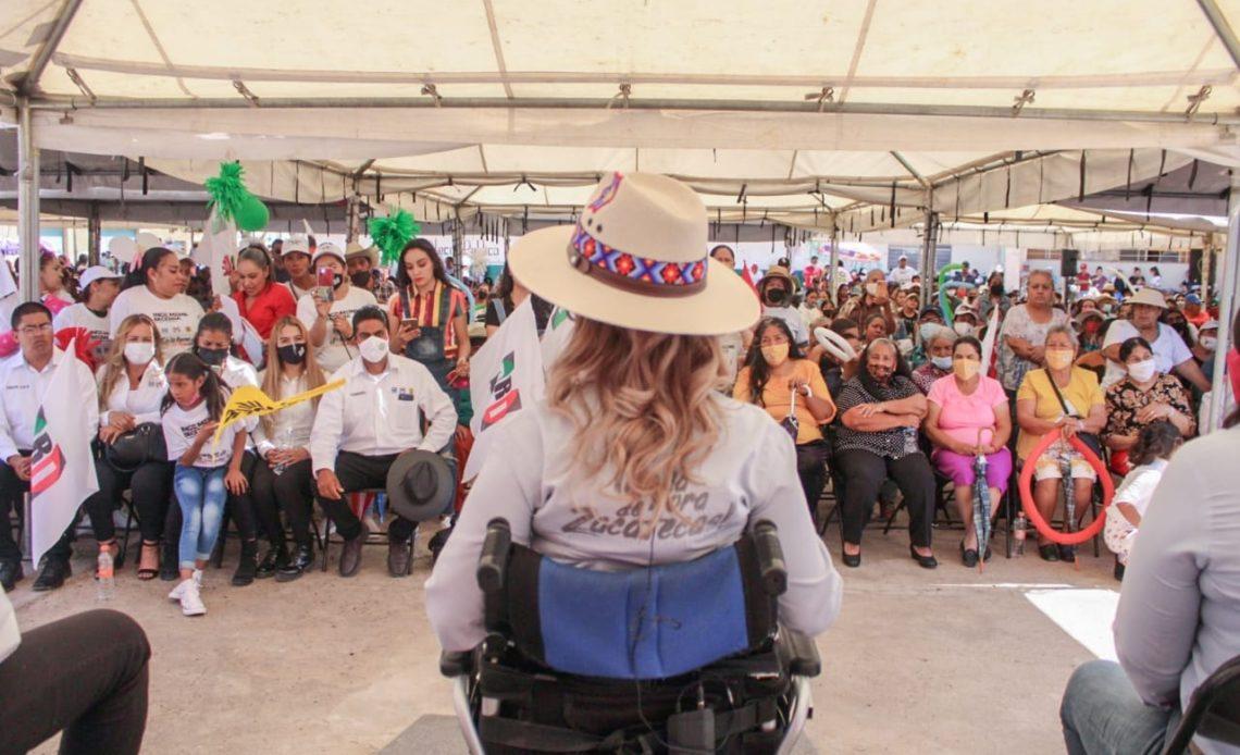 Fotografía en donde aparece Claudia Anaya, candidata con discapacidad motriz del estado de Zacatecas, aparece de espaldas, sentada en una silla de ruedas, es una mujer delgada con cabello largo, ondulado, de diferentes tonos de rubio que llega puesto un sombrero de paja con detalles bordados de diferentes colores alrededor de la cabeza, al frente de ella se encuentran varias personas, sentadas, debajo de una lona, todas utilizan cubrebocas y le prestan atención a la candidata.