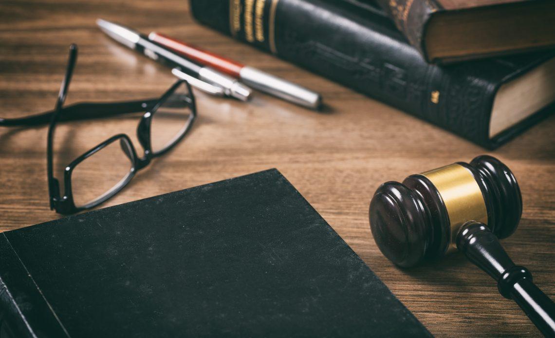 Fotografía de un libro de pasta negra sobre una mesa de madera, a un costado aparece un mazo de juez, ambos elementos pretenden representar gráficamente la idea de justicia.
