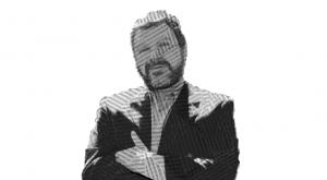 Fotografía de Diego Fonseca a blanco y negro con efecto de líneas sobre su rostro, un hombre de edad adulta con barba, rostro ovalado, con expresión sonriente, mira directo a la cámara y tiene los brazos cruzados, lleva puesto un saco y camisa.