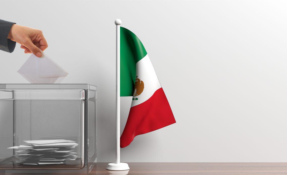 Fotografía de una urna de color gris en donde una mano inserta una boleta de color blanco, al costado aparece la bandera de Estados Unidos Mexicanos de color verde, blanco y rojo de izquierda a derecha y en medio tiene un águila parada sobre un nopal devorando una serpiente.