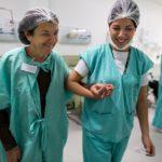 Fotografía donde aparecen dos mujeres en una sala de hospital, una mujer joven con cofia blanca, uniforme azul agua, camisa blanca, aparece sonriendo con el cubrebocas a la altura de la barbilla, sostiene la mano de la otra mujer de edad adulta que también sonríe. trae puesta una bata de hospital color verde mientras es guiada por la mujer joven.