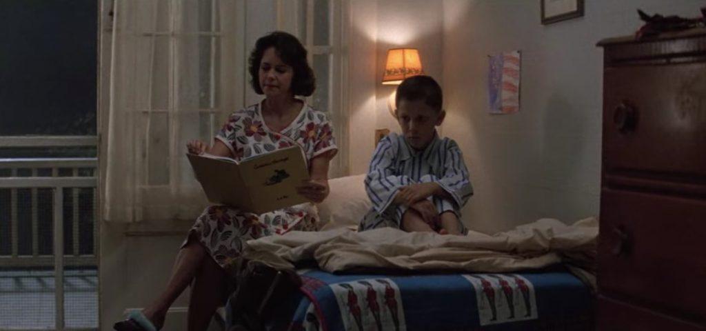Fotografía de una mujer con cabello castaño, corto a la altura de los hombros, que lee un libro sentada en la cama de una habitación, a su lado derecho se encuentra un niño, con pijama a rayas color azul con expresión serena mirando hacia el vacío de la habitación.
