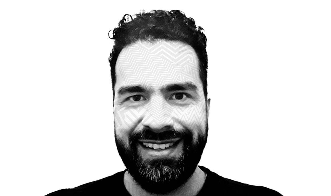 Fotografía a blanco y negro con efecto de líneas sobre el rostro de Carlos Celis, un hombre joven con barba y bigote, cabello rizado y corto que aparece frente a la cámara sonriendo.