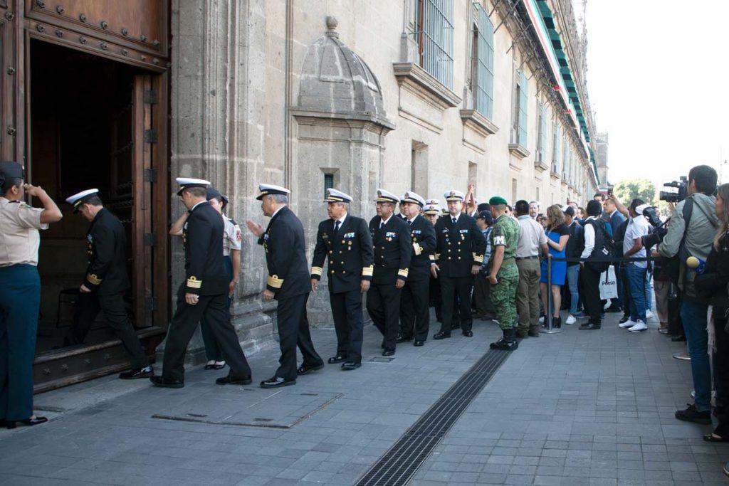 Fotografía de una fila de generales vestidos con uniforme oficial fuera de Palacio Nacional, a su alrededor se encuentra una multitud de gente y reporteros.
