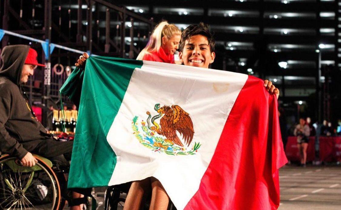 Fotografía de Luis Antonio Flores, quien muestra orgulloso una bandera mexicana. El joven está en su silla de ruedas y parte de su rostro está oculto por la bandera.