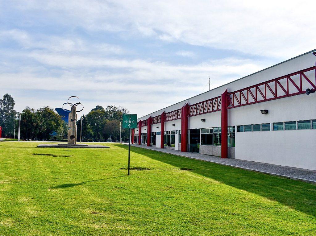 Fotografía de las instalaciones de un hospital, en donde aparece pasto verde frente a un edificio de color blanco con detalles rojos.