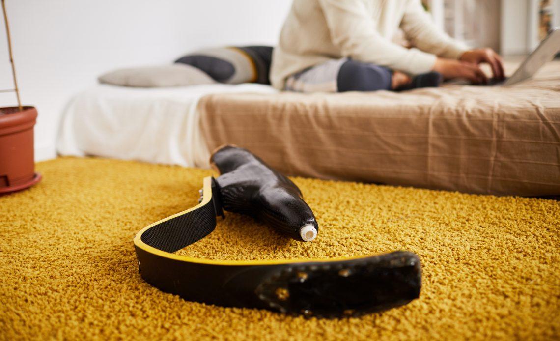 Fotografía de una prótesis de pierna en primer plano sobre una cama, al fondo, desenfocada, aparece una persona sentada con los pies cruzados sobre la cama con su computadora en el regazo.