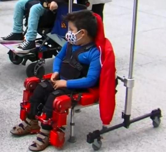 Un niño con cubrebocas, que viste una playera azul de manga larga y porta el peto del exeoesqueleto, aguarda sentado a la demostración que hará de esta estructura robótica color rojo que permitirá a niñas y niños con parálisis cerebral controlar su movilidad.