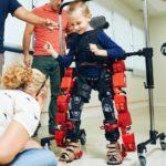 Fotografía que muestra a un niño pequeño muy feliz y sonriente durante una sesión en la que demostró el funcionamiento de un exoesqueleto. La estructura, color rojo, permite al niño moverse con libertad mientras cuatro adultos, uno de ellos una mujer en cuclillas, lo observan detenidamento.