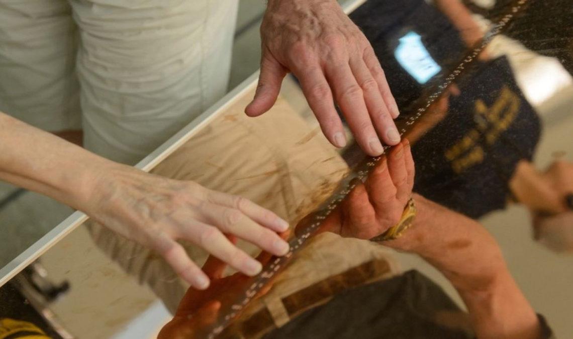Fotografía de unas manos tocando una superficie que forma parte de las guías interactivas del Museo Guggenheim para personas con discapacidad visual.