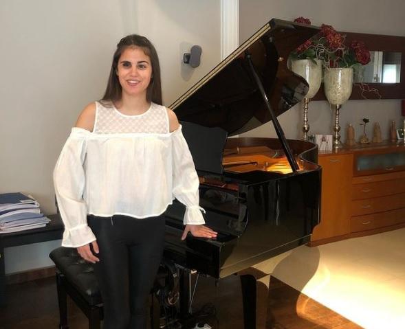 Fotografía de Laura Diepstraten, una mujer joven que aparece frente a un piano de cola color negro, ella va vestida con una blusa blanca con manga ancha y hombros descubiertos y un pantalón negro, tiene el cabello color castaño, ojos cafés, sonría frente a la cámara.