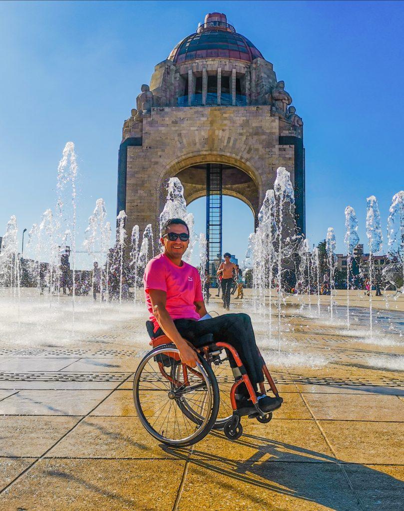 Fotografía de un hombre joven en silla de ruedas. lleva puesta una playera de color rosa y pantalones negros. trae lentes oscuros y sonríe frente a la cámara. Detrás de él aparece el monumento a la revolución ubicado en la CDMX, una infraestructura forma de arco con una cúpula hasta arriba.