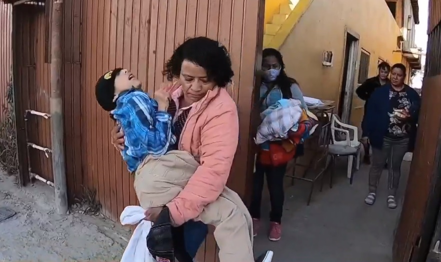 Fotografía de una mujer hondureña, de cabello oscuro, rizado y a la barbilla, y con una chamarra rosa, carga a su hijo de 14 años, quien tiene una discapacidad, para abordar un vehículo que los trasladará a la garita de San Ysidro, para ingresar a Estados Unidos. La escena es observada por tres personas, dos de ellas mujeres, familiares de la migrante centroamericana.