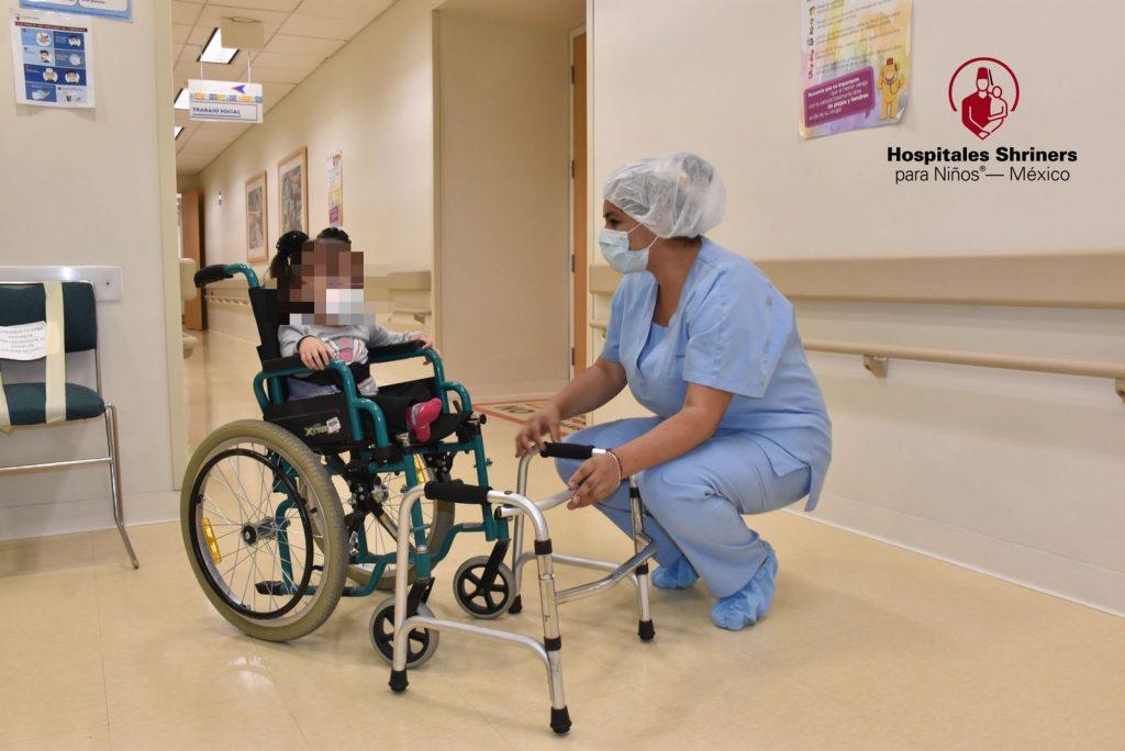 Fotografía de una sala hospitalaria en la que aparecen dos personas. La primera, un menor en silla de ruedas, y la otra es una enfermera en uniforme azul, con cubrebocas y gorro blanco, que está en cuchillas mientras parece platicar con el paciente.