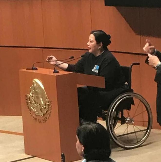 Fotografía de una mujer adulta de cabello negro, sentada en una silla de ruedas color negro, declamando un discurso frente a un atril de madera con el logotipo de los Estados Unidos Mexicanos en color dorado.