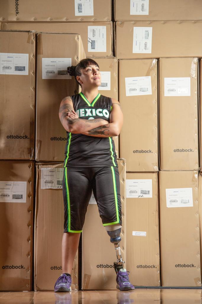 Fotografía de Yaotzaneth Díaz de León, una mujer joven deportista, con bermuda y playera sin mangas con tatuajes en ambos brazos, tiene una prótesis en la pierna izquierda, aparece con los brazos cruzados de pie frente a varias cajas de cartón.