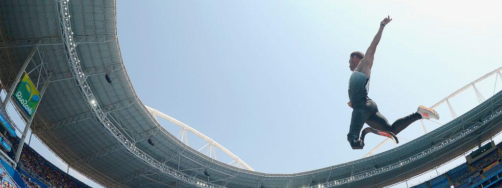 Fotografía de un hombre, atleta de gimnasia que se encuentra en un estadio de fútbol a contraluz, se ve su silueta, se encuentra saltando y trae puesto un uniforme de color gris y tiene una prótesis en su pie izquierdo.