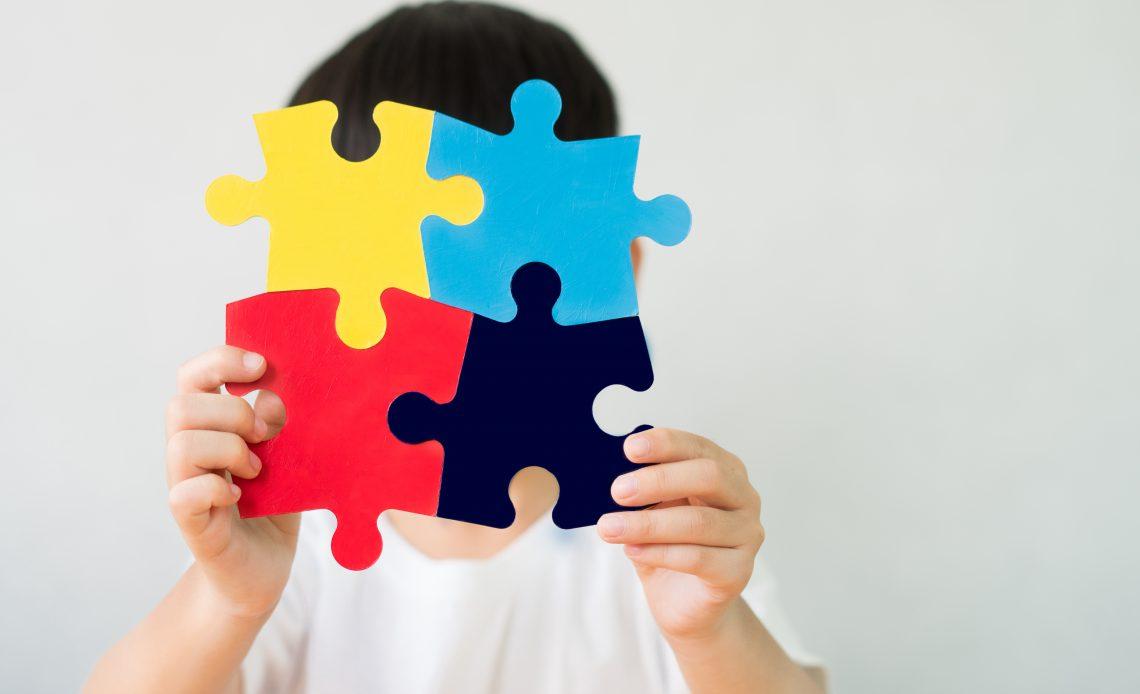 Fotografía de un niño de cabello negro que tapa su rostro con una figura que sostiene en sus manos compuesta de cuatro piezas de rompecabezas de colores azul cielo, azul rey, amarillo y rojo, el niño lleva puesta una playera de color blanca.