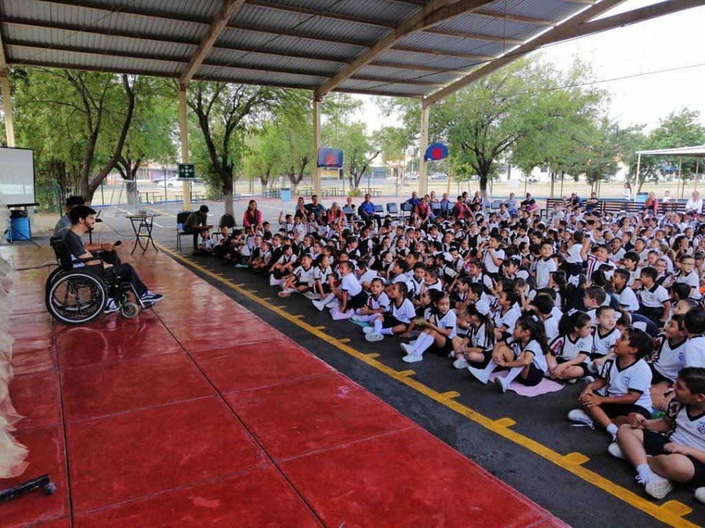 Fotografía de Adrián Ponce, un joven con aparente discapacidad motriz en silla de ruedas, lleva puesto un pantalón de mezclilla color negro, playera negra y sonríe frente a un público de aproximadamente 60 niños, uniformados de playera blanca y short negro, que escuchan con atención a su plática, todos se encuentran en medio de una cancha de fútbol.