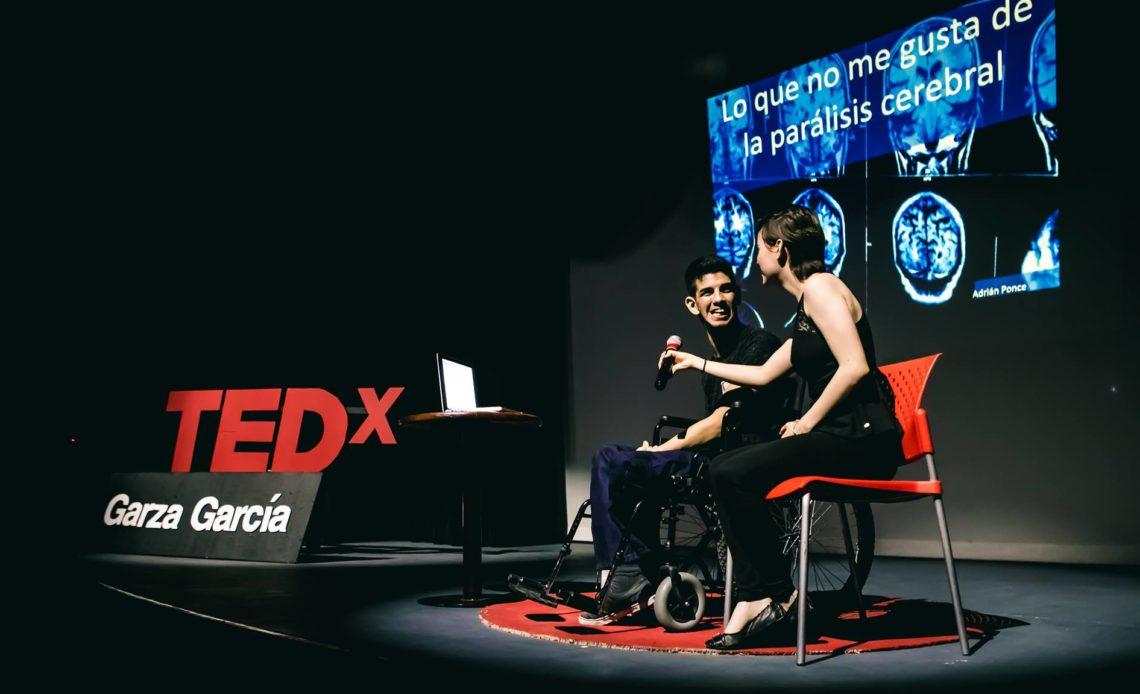 """Fotografía de Adrián Ponce, un joven con aparente discapacidad motriz en silla de ruedas, lleva puesto un pantalón de mezclilla color azul, playera negra y sonríe frente a un podium de Tedex, a su lado, una mujer joven, vestida con un palazzo de color negro, a la que no se le nota el rostro, le ayuda a sostener un micrófono frente a su rostro. Detrás aparece una presentación de una resonancia de cerebro que dice: """"Lo que no me gusta de la parálisis cerebral""""."""