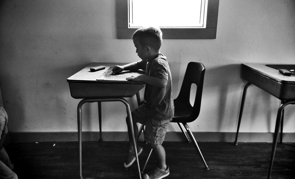 Fotografía a blanco y negro de un niño sentado en una banca escolar, coloreando sobre su escritorio, se encuentra frente a ventana.