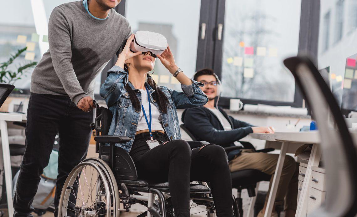 Fotografía en la que aparece una mujer joven, cabello castaño, pantalón de meclilla de color negro, blusa blanca y chaqueta de mezclilla color azul, sentada en una silla de ruedas, que lleva puestos unos lentes de realidad virtual color blanco sobre sus ojos