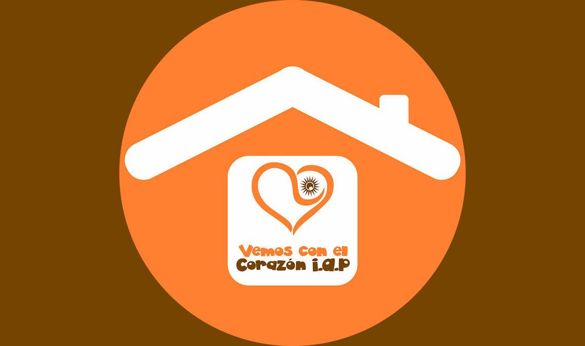 """Imagen con el logotipo de la Fundación Vemos con el Corazón, el techo de una casa de color blanco, debajo de el techo, de color naranja y café el texto """"Fundación Vemos con el Corazón""""."""