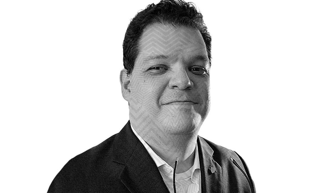 Fotografía a blanco y negro con efecto de líneas sobre el rostro de Agustín De Pavía Frías un hombre de edad adulta, cabello corto, ojos grandes y rostro ancho, que viste un saco formal y luce serio frente a la cámara.