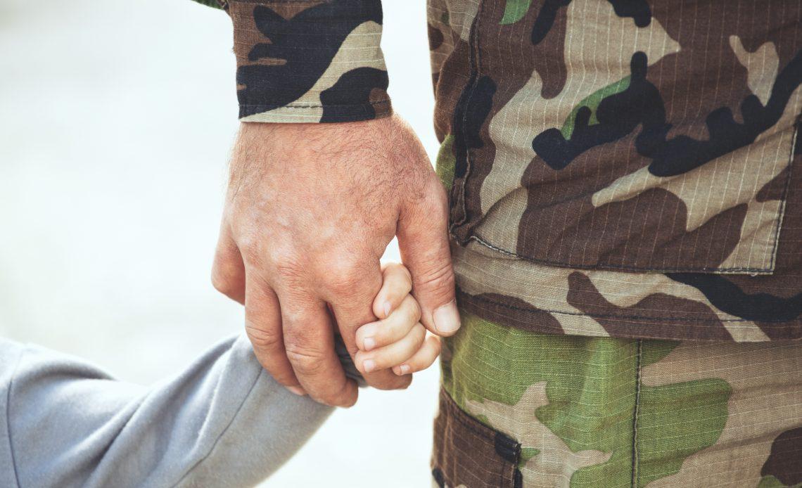 Fotografía en donde se aprecia la mano de un hombre vestido de traje militar de diferentes tonalidades de color verde, tomando la mano de un niño con suéter gris, no se alcanza a apreciar su rostro, sólo sus manos entrelazadas.