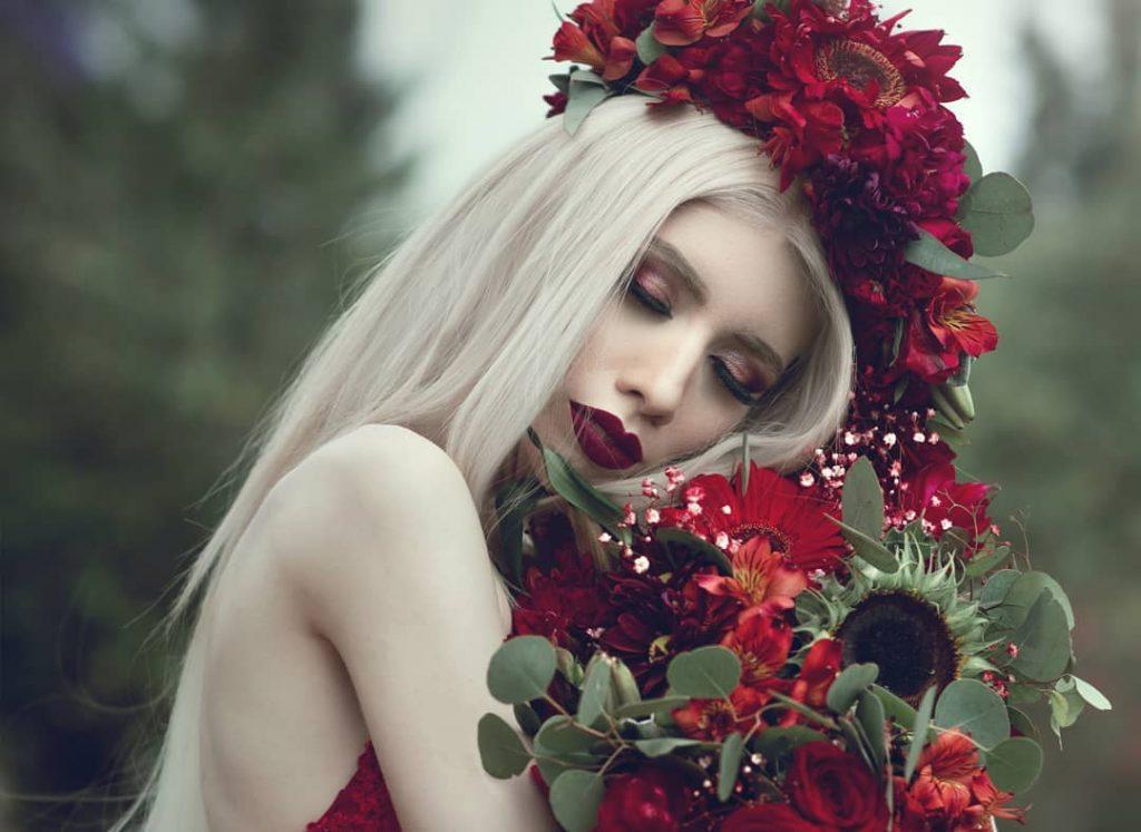 Fotografía de Ruby Vizcarra, una mujer joven de tez blanca, cabello de color blanco, col los labios pintados de color rojo, sostiene cerca de su rostro un ramo de rosas rojas con algunas plantas de color verde al rededor de las mismas, su cabello está peinado en forma de chongo con una trenza suelta al rededor.