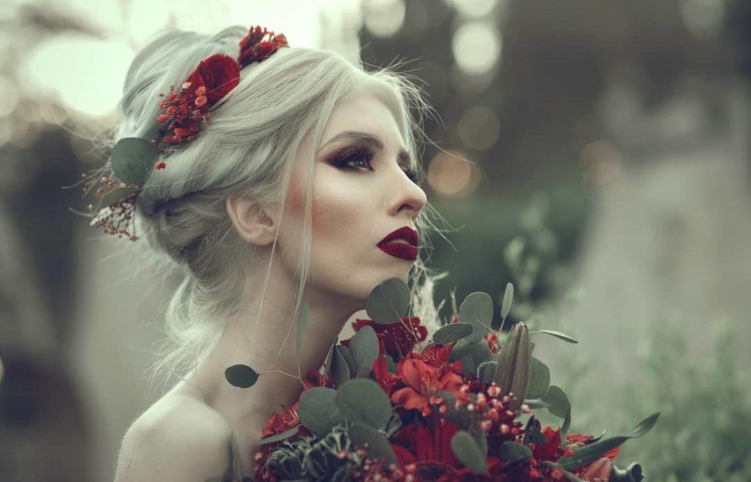 Fotografía de Ruby Vizcarra, una mujer joven de tez blanca, cabello de color blanco, con los labios pintados de color rojo, sostiene cerca de su rostro un ramo de rosas rojas con algunas plantas de color verde al rededor de las mismas, su cabello está peinado en forma de chongo con una trenza suelta al rededor.