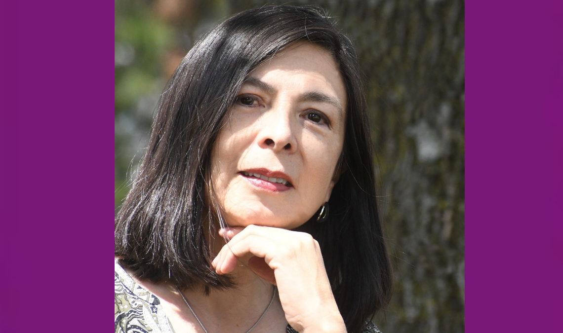 Fotografía de Celia Facio, una mujer de mediana edad y cabello lacio, color negro, que le llega abajo de la barbilla. En la imagen solo se aprecia su rostro, sonriente, y una de sus manos que se recarga suavemente en la barbilla.