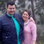 Imagen de un hombre joven y una mujer, son madre e hijo y están abrazados y sonríen. El joven viste una chaqueta azul marino y una playera color verde agua. La mujer viste un conjunto de rayas horizontales rosa con blanco.