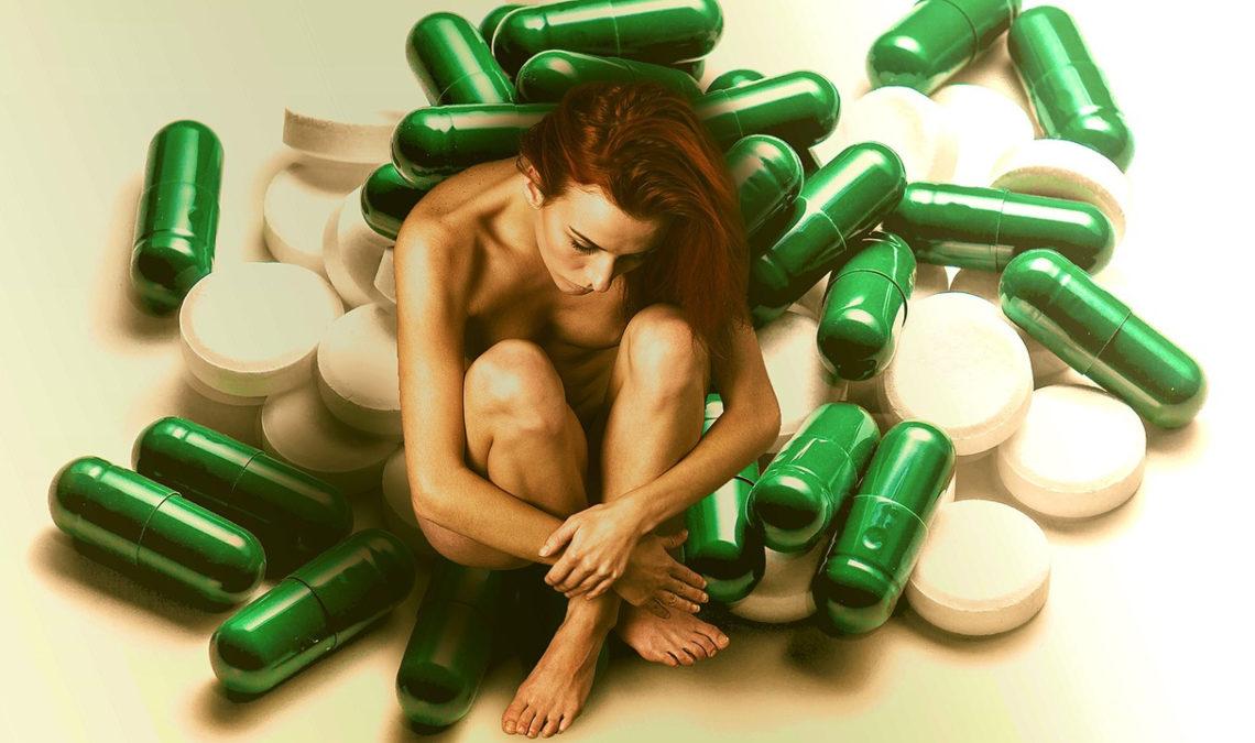 Composición fotográfica en la que se aprecia a una mujer joven, en el centro de la imagen Ella está desnuda, sentada con las piernas dobladas y sus brazos las sostienen. Tiene la espalda encorvada y su rostro y mirada hacia abajo. Solo se ve la mitad del rostro, aunque no se aprecian bien sus facciones. Tiene el cabello largo, ondulado, y todo cae de lado. La mujer esta rodeada de cápsulas verdes y pastillas blancas, en gran formato, es decir, una cápsula es del tamaño de su brazo, por ejemplo.